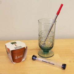 Tradeshow giveaways include a metal drinking straw and small pot with herb seeds