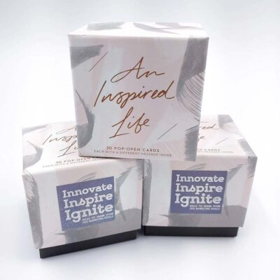 A stack of three boxes that each contain 30 pop-open cards, each with a different inspirational message inside.