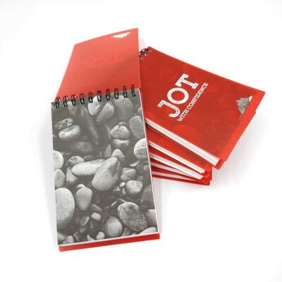 A stack of notepads with the words Jot With Confidence printed on the cover.
