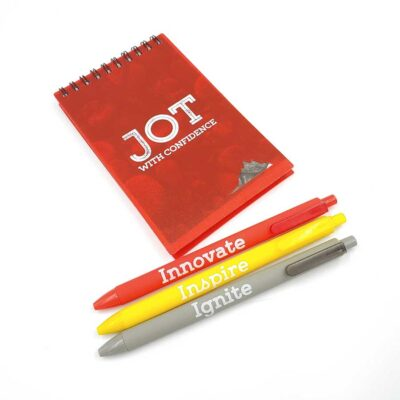 A notepad with the words Jot With Confidence printed on the cover and three pens next to it, each with the words Innovate, Inspire and Ignite printed on them.