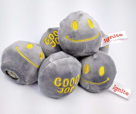 Plush stress balls with a smiley face embroidered on one side and the words Good Job on the other.