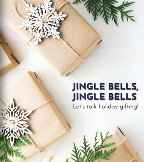 Brown paper wrapped gifts embellished with wooden snowflake ornaments and pine greenery and the accompanying text, Jingle Bells, Jingle Bells, Let's Talk Holiday Gifting.